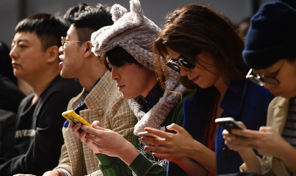 A group of people looking at their mobile phones